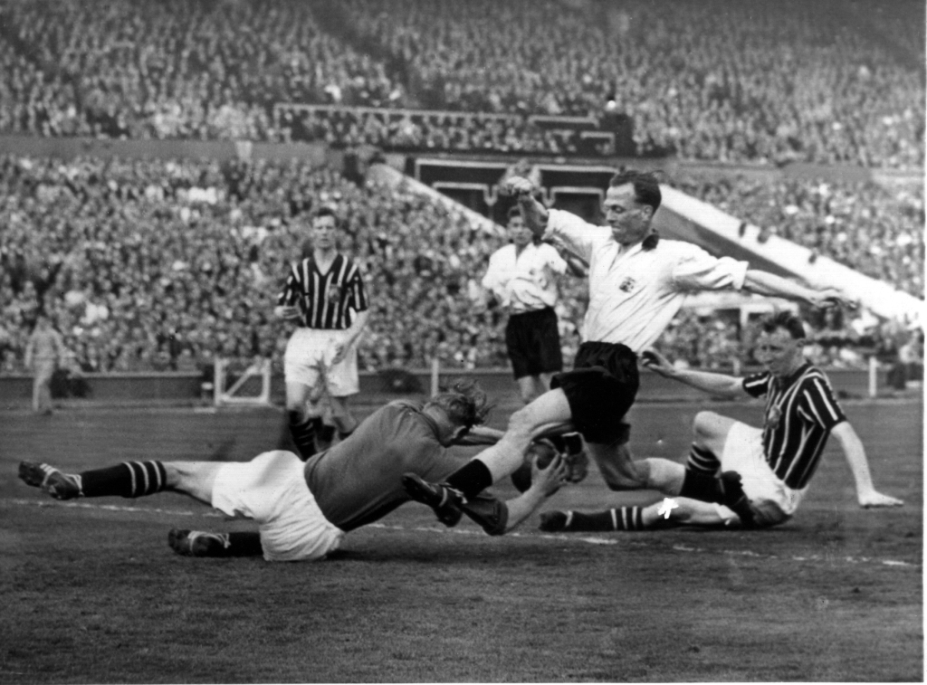 Bert Trautmann dives for the ball moments before the collision which left him with a broken neck, during the FA Cup 1956