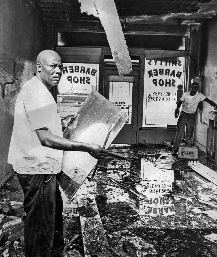 Aug. 17, 1965: A. Z. Smith, left, begins the task of getting Smitty's Barber Shop on Beach St. back in shape following the Watts Riots. Business establishments owned by whites were the usual targets of looters and arsonists. Smith was one of the few blacks caught up in the turmoil. (photo: R. L. Oliver / Los Angeles Times)