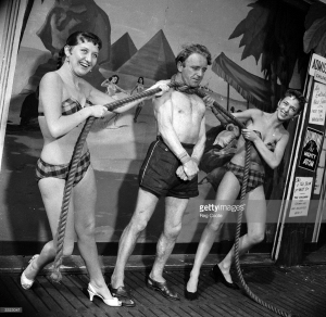 Mike Costello, aka Blondini, demonstrates the muscular strength of his neck as a rope is tightened around his neck by his bikini-clad assistants. (Photo by Reg Coote/BIPs/Getty Images)