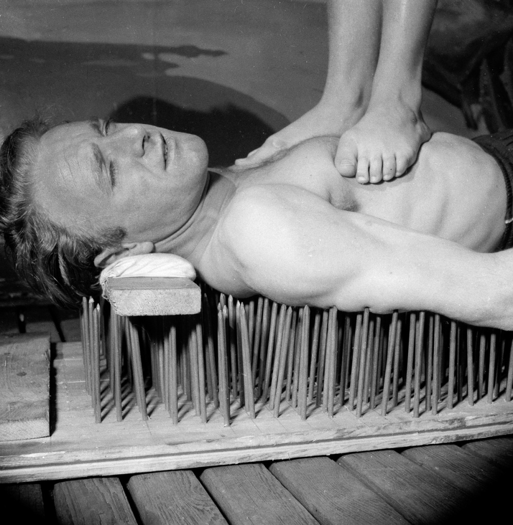 1955:  Mike Costello, otherwise known as Blondini or the White Yogi, lying on a bed of nails whilst balancing a woman on his chest.  (Photo by Reg Coote/BIPs/Getty Images)