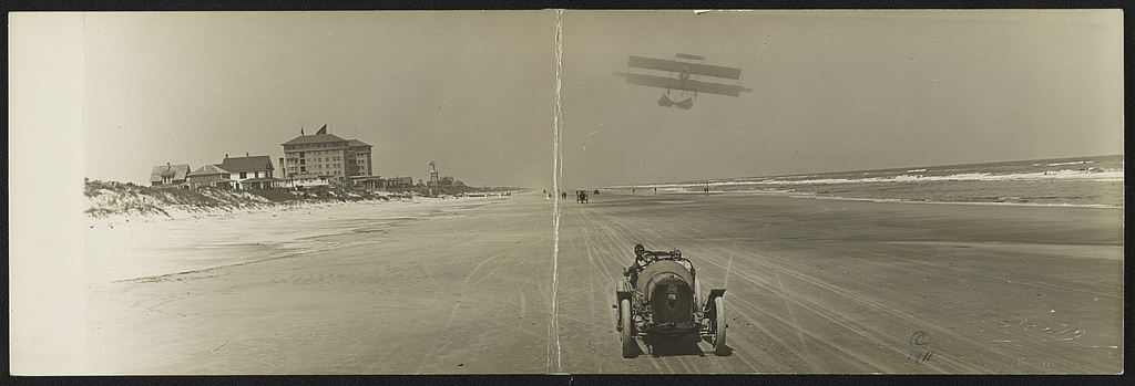 Cars on beach with airplane overhead and Clarendon Hotel in background, Seabreeze, Daytona Beach, Florida, 1911 (William H. Gardiner / Library of Congress)