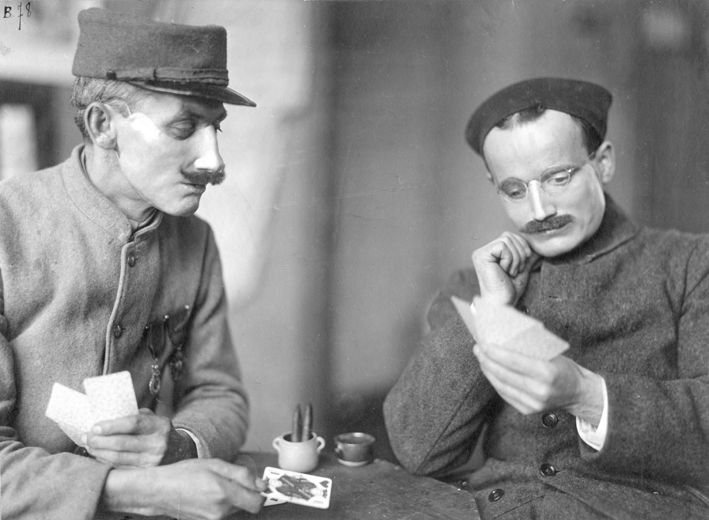 Soldiers Caudron and Cavalliet are playing cards, while wearing Ladd's Portrait Masks (American Red Cross) 1918