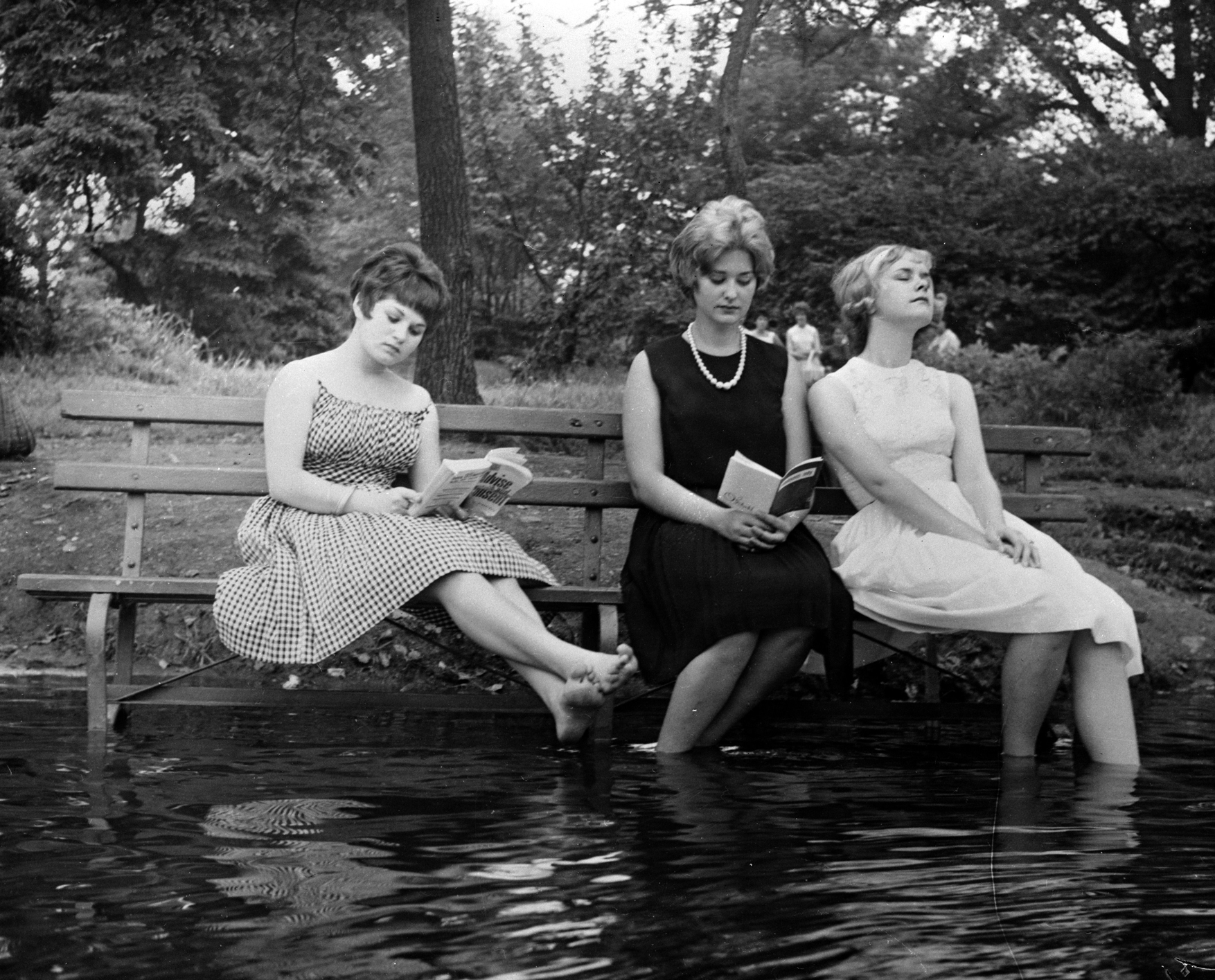 September 1961: Three women keep cool during a heat wave by moving a park bench into the water in Central Park, New York. (Photo by Keystone Features/Getty Images)